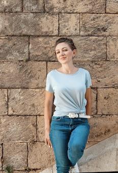 Tシャツとジーンズを着ている女性は通りの屋外の壁の近くに滞在します