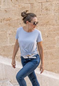 Tシャツ、ジーンズ、日よけを着て階段を上り、晴れた夏の日に屋外を振り返る女性