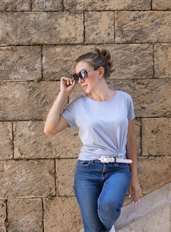 Women wearing t-shirt and jeans stays near a stone wall and looks left, outdoor in a sunny summer day