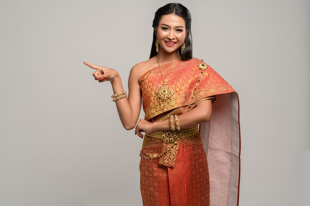 Women wearing thai costumes that are symbolic, pointing fingers