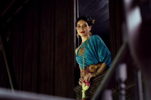 タイの民族衣装を着た女性がタイの家の窓のそばに立っている