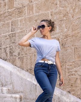 Women wearing tshirt jeans and sunglases going down the stairs and looking back outdoor