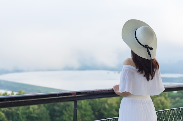 Women wearing a white brimmed hat standing back to watch the view.