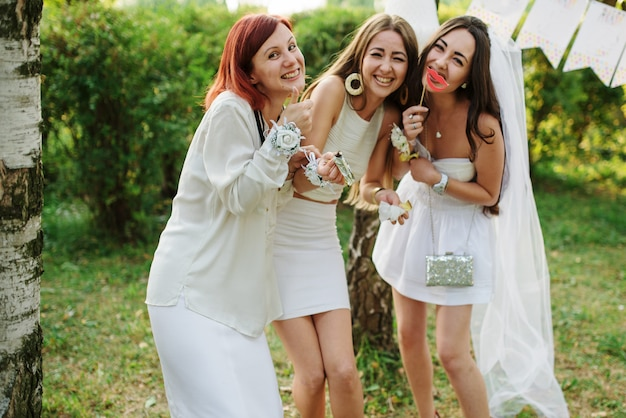 Women wearing on white dresses having fun on hen party.