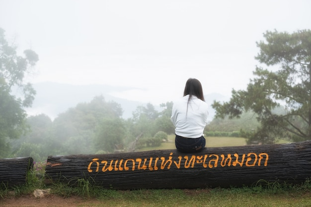 Women wearing a white shirt sitting on a stick,looking at the sea of fog