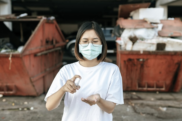 젤을 눌러 손을 씻기 위해 손을 씻는 흰색 셔츠를 입은 여성.
