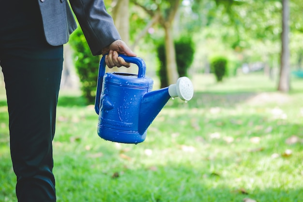 Women wearing a work suit holding a watering can in the garden