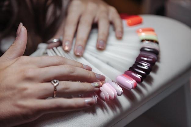 手入れの行き届いた女性の手は、美容院でネイルカラーのサンプルを選びます。爪の色のパレットと白いテーブルの上の女性の手。ネイルトリートメントとケア。スタイルと美しさの満足の概念