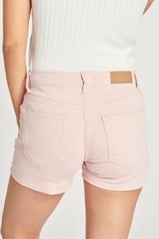 Top corto da donna bianco e mockup di jeans corti rosa chiaro