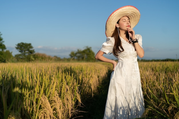 Women in the white dress enjoy natural  in  golden rice field.