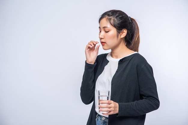体調が悪く、抗生物質を服用しようとしている女性。