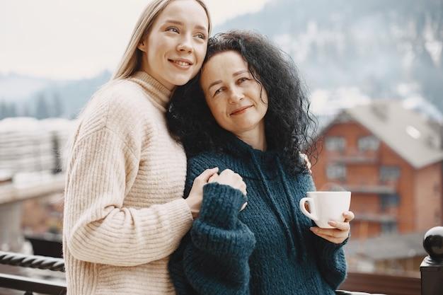 커피 한잔과 함께 여성. 산에서 멋진 휴가. 눈 덮인 날씨.
