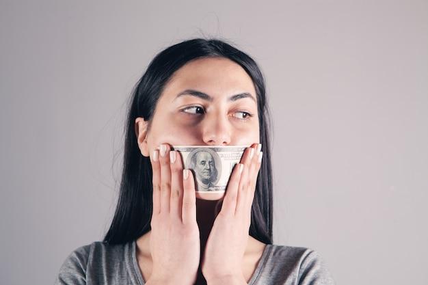 ドル紙幣を口にした女性