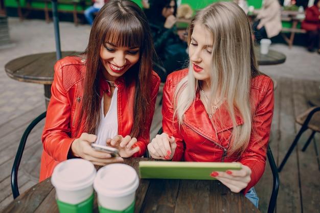 Женщины с помощью смартфона и планшета в кафе