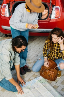 Women with backpack and smartphone near man looking at map near car