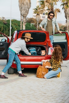 Women with backpack near car trunk and man leaning out from car