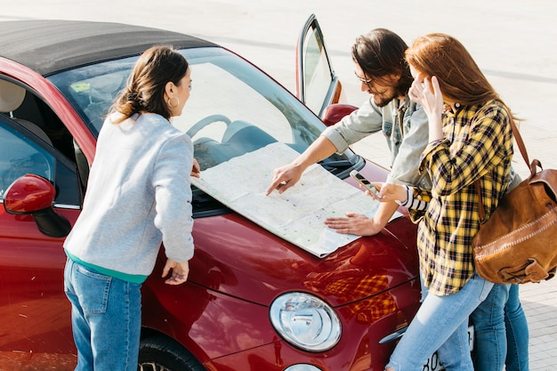 Women with backpack and smartphone near man looking at map on car hood