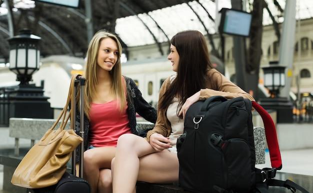 역에서 기차를 기다리는 수하물을 가진 여성