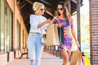 Women with bags looking at smartphone and going on shopping street
