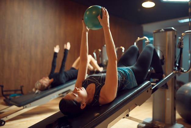 ジムでのピラティストレーニングでボールを持っている女性、柔軟性。スポーツクラブのフィットネスワークアウト。