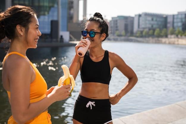 バナナと水のミディアムショットを持つ女性