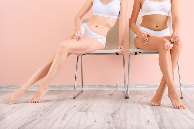 Женщины с красивыми ногами после депиляции возле цветной стены