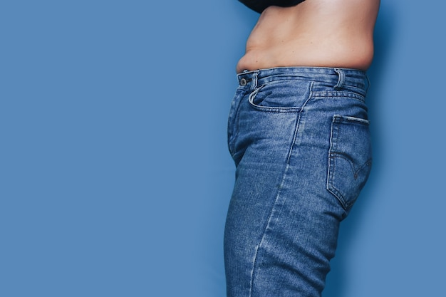 Women with belly fat standing in jeans on blue