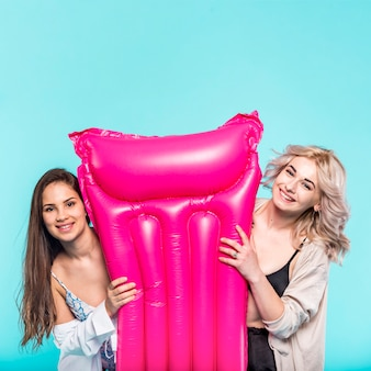 Women with bright pink pool air mat