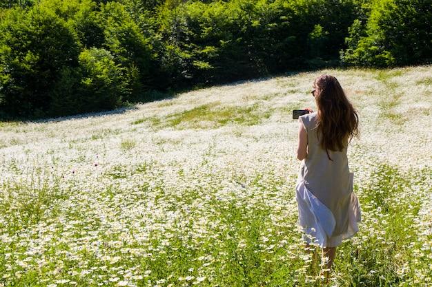 Женщины с платьем в поле цветов ромашки во время солнечного света