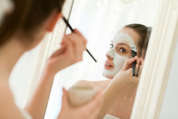 顔の化粧品を持つ女性