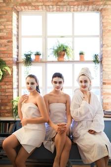 Le donne con prodotti cosmetici per il viso