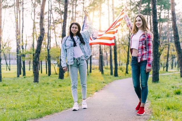 屋外を歩くアメリカの国旗を持つ女性