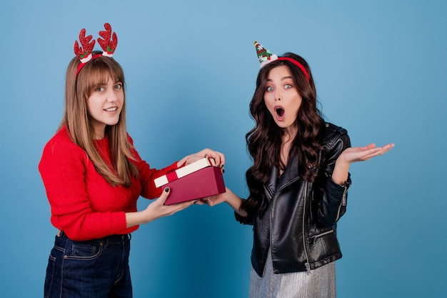 Women with gift box with ribbon wearing funny christmas hoops