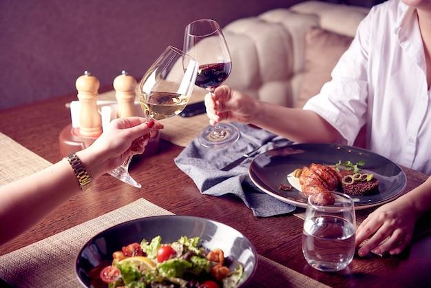 Женщины с бокалами красного и белого вина на ужине или обеде в роскошном ресторане