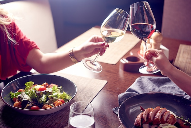 고급 레스토랑에서 적포도주와 백포도주 한 잔을 들고 사업 아이디어에 대해 토론하는 여성