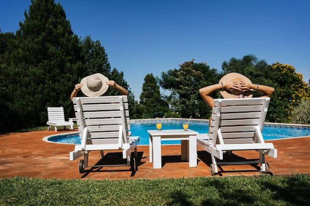 Женщины в шляпах сидят на шезлонгах, загорают у бассейна.