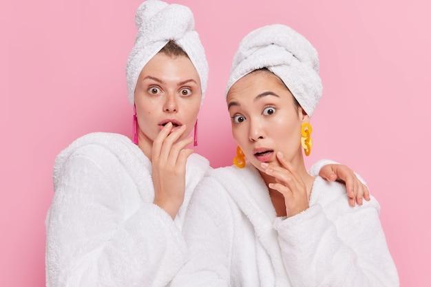 頭に白い柔らかいバスローブタオルを着た健康的な輝く肌の女性は、ピンクに対して互いに密接に立っていることに非常に驚いています
