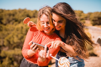 Women with lollipops using smartphone