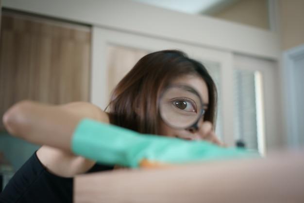 コロナウイルスまたはcovid-19保護用のスプレー消毒剤でテーブルを掃除している虫眼鏡の女性。