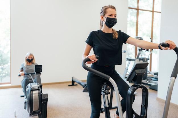 체육관에서 유행성 운동을하는 동안 의료 마스크를 가진 여성