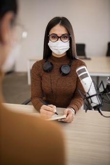 ラジオ番組をしている医療用マスクを持つ女性
