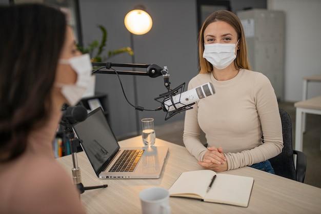 ラジオスタジオで医療用マスクを持っている女性