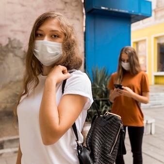 屋外で列に並んでいる医療用マスクを持つ女性