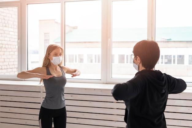 屋内でトレーニングしている医療用マスクを持つ女性