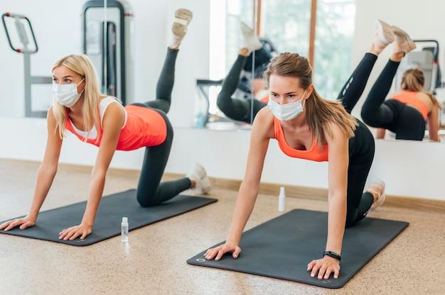 Женщины в медицинских масках вместе тренируются в тренажерном зале