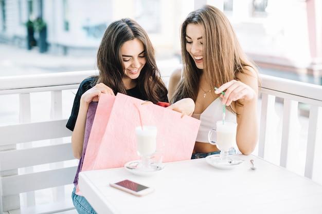 Women with milkshakes looking at paper bag