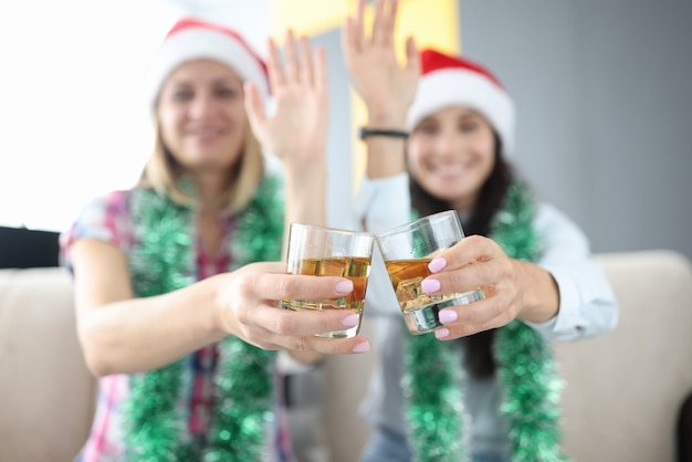 Женщины с новогодними украшениями и в новогодних шапках держат в руках бокалы с алкоголем и машут