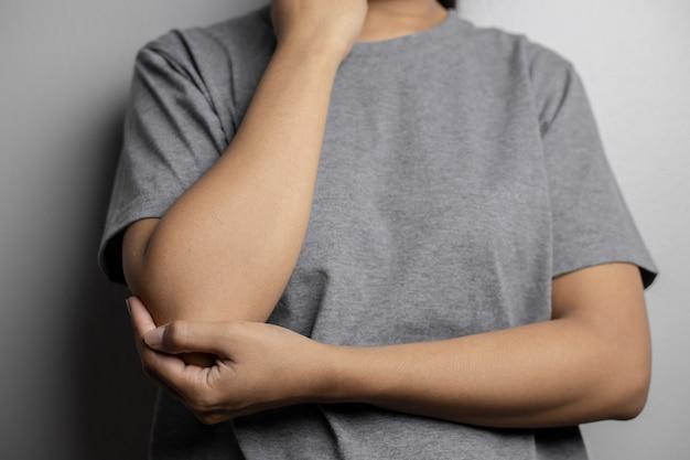 팔꿈치에 통증이 있는 여성. 팔꿈치의 급성 통증. 젊은 여자는 팔꿈치를 보유합니다.