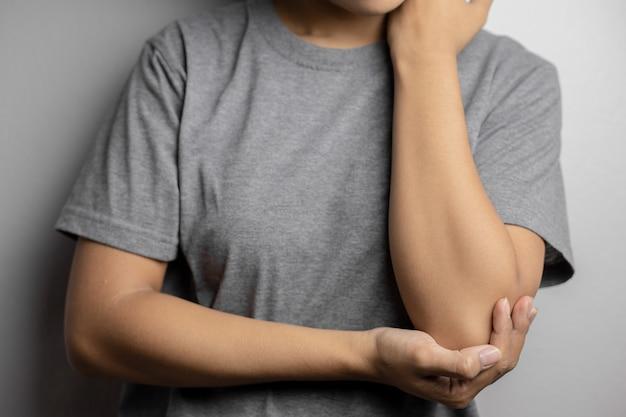 Женщины с болью в локте Premium Фотографии