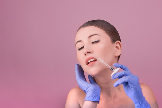 Women with perfect skin posing holds a syringe in their hand. conceptual image of plastic surgery victims